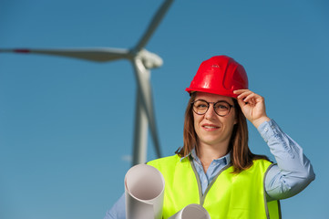 Portrait of a beautiful young female engineer in red helmet and glasses with projects and plans against the background of a windmill and blue sky