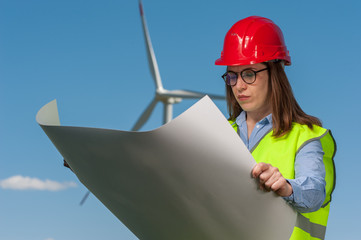 Serious young woman engineer looking at a plan of repair work on the background of a windmill