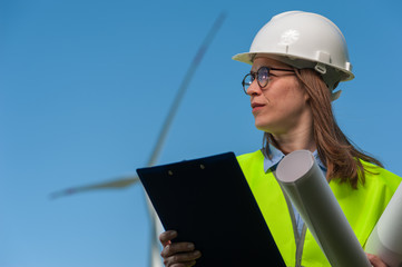 Portrait of a successful young female architect in a safety helmet with a work plan and projects on a background of windmills and blue sky.