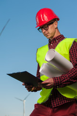 Portrait of a ambitious young male engineer in a safety helmet with a work plan and projects on a background of windmills and blue sky.
