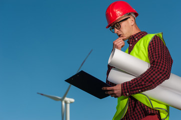 Portrait of a serious ambitious engineer with a helmet with an engineering plan in his hands against the backdrop of a windmill and a blue sky.