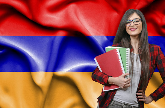 Happy female student holdimg books against national flag of Armenia