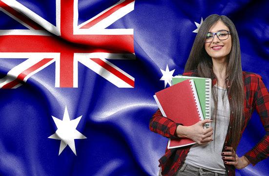 Happy female student holdimg books against national flag of Australia