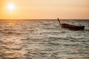 One boat floating in the ocean during the sunrise.