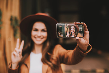 Amazing and positive young woman is standing ans posing on camera. She is taking selfie. Girl smiling and showing piece symvol with fingers. Woman is happy