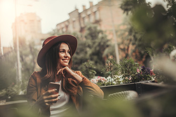 Attractive woman sitting outside and holding phone in hands. She is posing and looking to the right. Girl is smiling. Beautiful woman is chilling and relaxing