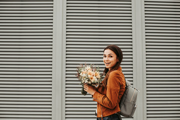 Excited and happy girl is holding flowers in hands. She is looking on camera and smiling. She is posing. Woman wears brown jackeet and grey bag. Isolated on striped and white background