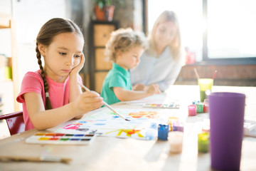 Concentrated little girl sitting at the table and painting picture with young woman and boy in the background