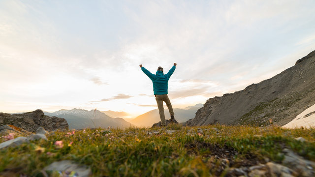 Man standing on mountain top outstretching arms, sunrise light colorful sky scenis landscape, conquering success leader concept.