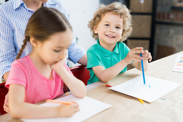 Smiling cute little boy drawing with color pencil together with girl at the table