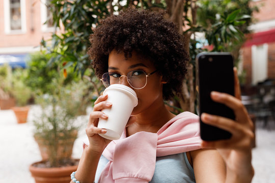 Female blogger taking a selfie on smartphone while drincking a coffee