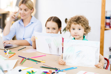 Portrait of two cute kids sitting at the table and showing their own pictures to the camera with teacher talking on phone in the background