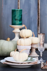 Thanksgiving Day or Halloween place setting with heirloom mini white and grey pumpkins and candles against a rustic autumn background.
