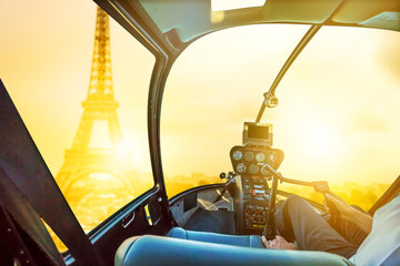 Helicopter cockpit flying on Place du Trocadero in French capital, Europe. Scenic flight above Eiffel Tower and Paris skyline on sunset background.