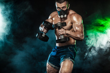 Muscular young fitness sports man, bodybuilder in training mask. Workout with dumbbell in fitness gym