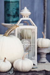 Autumn decorations with heirloom mini and large white pumpkins and candles against a rustic autumn background. Thanksgiving Day or Halloween Decor.