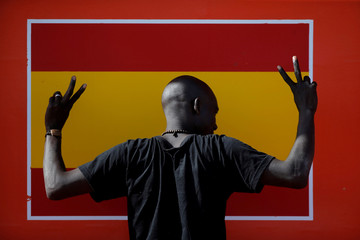 A migrant gestures next to a Spanish flag on a rescue boat after arriving at the port of Algeciras