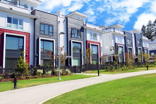 Beautiful new contempory suburban attached townhomes with colorful summer gardens in a Canadian neighborhood.