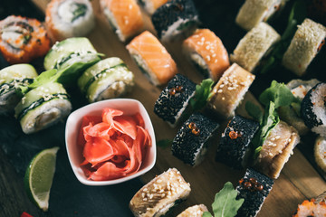 Sushi set food photo. Rolls served on brown wooden and slate plate. Close up and top view of sushi. Vintage toning image