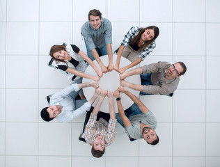 smiling business team folded their hands forming a circle