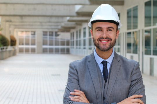 Engineer with white helmet smiling in office space