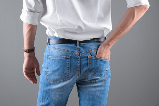 Man in stylish blue jeans on grey background