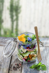 Vegan salad in a jar: vegetables,and flowers,pasta, smoked salmon, for a healthy homemade raw food concept.on blury greeny wall