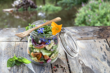 Vegan salad in a jar: vegetables,and flowers,pasta, smoked salmon, for a healthy homemade raw food concept. river background