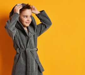 Boy kid standing in gray bathrobe looking at the corner on yellow