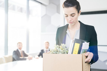 Waist up portrait of sad businesswoman holding box of personal belongings  leaving office after being fired job, copy space