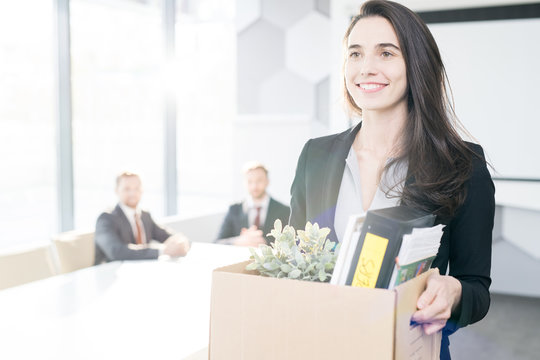 Waist up portrait of happy young businesswoman holding box of personal belongings  leaving office after quitting job, copy space