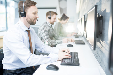 Side view portrait of handsome bearded man wearing headset  working with group of help desk operators sitting in row, copy space