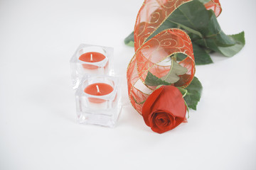 two candles and a red rose on a white background.photo with copy