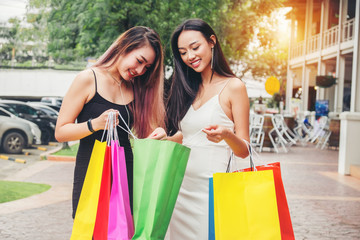 Happy Asian women friendship Enjoying Spending shopping bags in Fashion shopping street