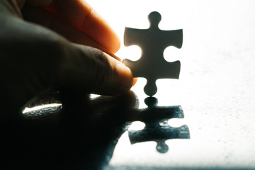 Business problem, obstacle and solution for success metaphor, hand holding a paper jigsaw puzzle piece with hoping sun light, the one that solve problem