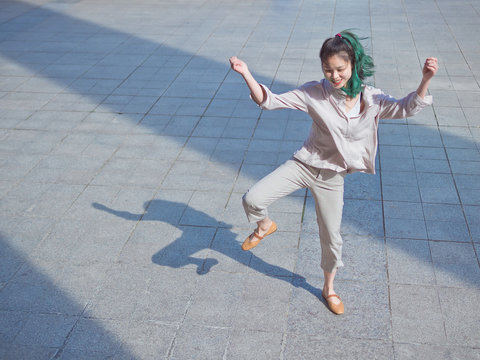 Beautiful young girl with green hair dancing outdoor with black silhouette shadow on ground. Sunny portrait of glamour Chinese stylish lady. Emotions, people, beauty and lifestyle concept.