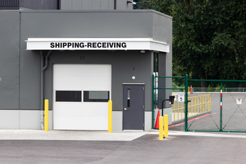 Warehouse building shipping receiving garage door and gate with road driveway
