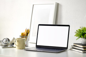 Minimal desktop, white workspace with laptop computer, poster frame and books.