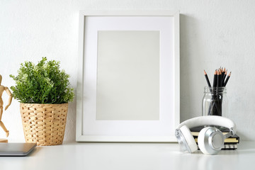 Blank poster with office stuff on white wooden table.