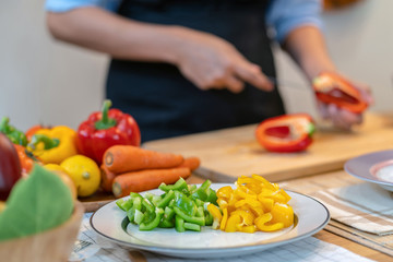 Closeup Bell pepper over the photo blurred of chef are cut the bell pepper on the Chopping board in modern kitchen, diet and healthy food concept