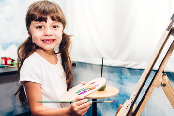 Little girl artist drawing on canvas with color palette and watercolor paints at home