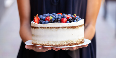 The girl is holding a cake with forest berries, strawberries, blueberries, on the street in the city. A concept for the production of cakes, bakeries, restaurants. Background image