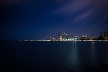 A evening skyline view of Chicago with star trails and moving clouds