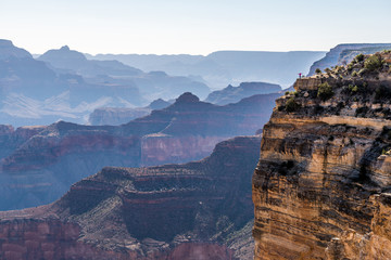 Girl in Jeans Suite is Standing on the Edge of Grand Canyon and Meeting Sunrise