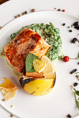 English cuisine. A steak of red fish salmon or trout lies on a pillow of spinach with cream, with lemon and cinnamon stick. Copy space, selective focus
