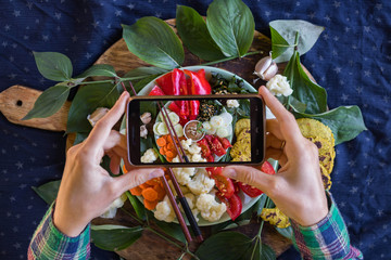 Smartphone food photography of vegetables Buddha Bowl for lunch or dinner. Woman hands takes trendy phone photo of food. Good for blogging or social media. Vegan vegetarian food