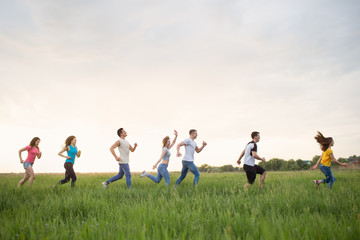 Group of people running in the grass,