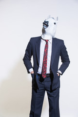 A man in a suit and a horse mask on a light background. Conceptual business background