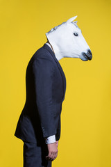A man in a suit and a horse mask on a yellow background. Conceptual business background