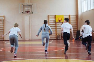 Primary school children a sport lesson indoors
